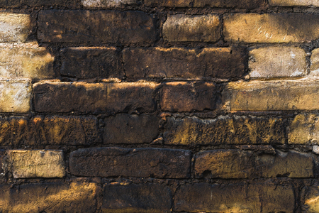 Close-up Textured background of old faded bricks stained with black oil. A brick gradient between dirty black and light yellow bricks. Grunge style