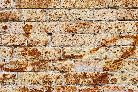 Background wall from an ancient yellow vintage brick with rusty corrosion patterns on the surface. Textured background in grunge style. Procurement for stylish graffiti