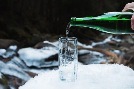 Mineral mineral water is poured from a glass green bottle into a clear glass beaker.