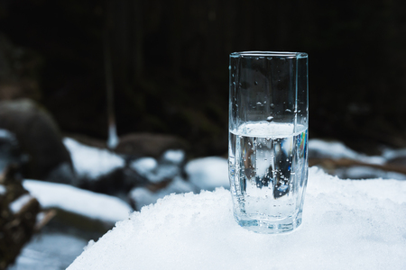 A transparent glass glass with drinking mountain water stands in the snow against a background of a clean frost mountain river in winter. Stock Photo