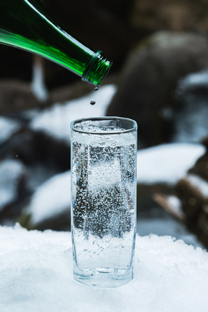 Pure mineral water is poured from a glass green bottle into a clear glass beaker until the last drop. Stock Photo