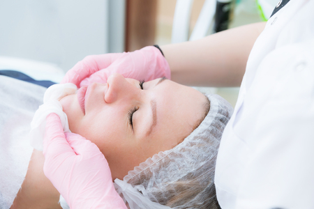 A close-up of the cleaning procedure in the office of cosmetology. The hands of the cosmetologist in pink gloves are removed from the face of a young girl with a sponge cleansing the mask