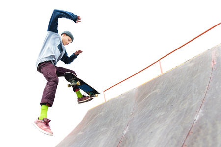 The teenager skateboarder in the cap does a trick with a jump on the ramp in the skatepark. Isolated skater and ramp on white background Stock Photo