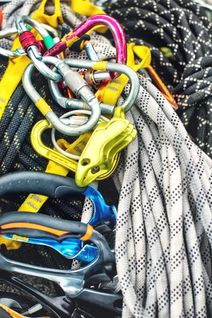 Used climbing equipment - carabiner without scratches, climbing hammer, white helmet and grey,red,green and black rope Stock Photo