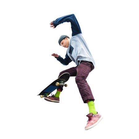 A teenage boy in a hat and a sweatshirt jumping with a skateboard does a trick on an isolated white background. The cut out character the preparation Stock Photo