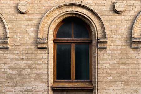 Vintage arched window in the wall of yellow brick. Black glass in a maroon dark red wooden frame. The concept of antique vintage architecture in building elements. Stock Photo
