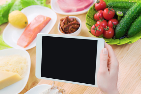 Close-up top view of female hands holding a tablet computer with a blank display surrounded by healthy food on a home kitchen table.