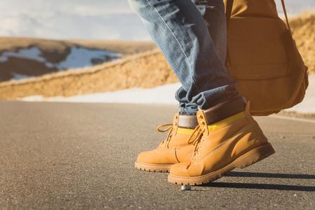 Marcher sur le coucher de soleil d'été sur l'asphalte, les jambes d'hommes en chaussures jaunes et jeans bleu longent l'asphalte. À côté du sac à dos vintage. Concept d'auto-stop.