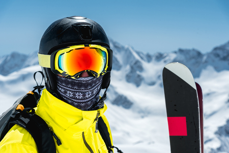 A large portrait of a skier in a protective helmet and glasses - a mask and a scarf next to the skis against the snow-capped mountains of the Caucasus. Skiing