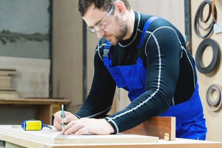 A bearded tired handsome carpenter on a table with a pencil draws a sign on the board. At the workplace there is an ordinary master dressed in blue cambenizon with a cruel haircut and saved glasses. The concept of garage furniture production