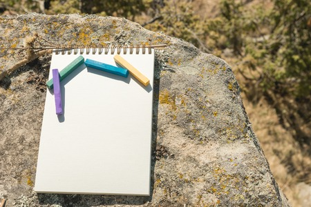 Close-up artwork for the designer. A blank notepad for drawing pastel on which lay an artistic pastel crayons color chalks of purple green blue and yellow lies on a rock in nature outdoors. The concept of creativity and unity with nature Stock Photo