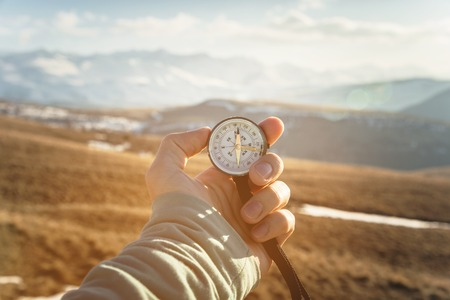 a mans hand holds a hand-held compass against the backdrop of mountains and hills at sunset. The concept of travel and navigation in open areas
