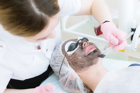 The cosmetologist in pink gloves with a brush applies a carbon mask for peeling on the face of a young girl in a cosmetology room. The concept of cosmetology services and self-care. The concept of maintaining youth and beauty Stock Photo