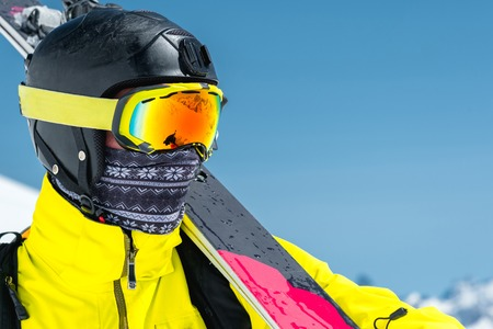 A lclose-up portrait of a skier in a protective helmet and glasses is a mask and scarf with skis on his shoulder in the snow-capped mountains of the Caucasus. Skiing, Stock Photo