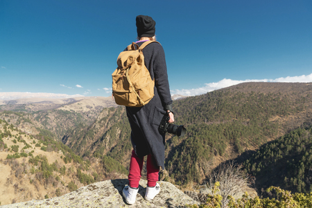 A travel photographer girl hipster in a hat and with a backpack standing on a rock and looking at the hills.