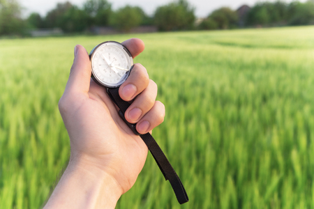 Finding a direction in nature on a wheat field. A mans hand holds a compass Stock Photo