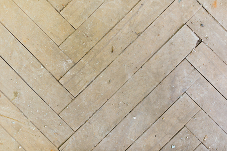 A close-up of an old gray faded parquet covered with dust and dirt. Result of repair. Cleaning and cleaning required