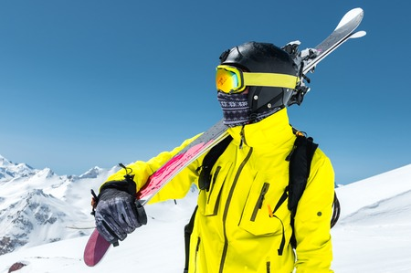A large portrait of a skier in a protective helmet and glasses is a mask and scarf with skis on his shoulder in the snow-capped mountains of the Caucasus. Skiing, Stock Photo