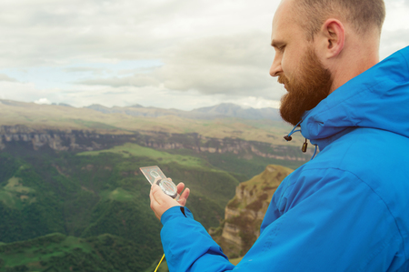 Hipster man in a blue jacket using a compass on the background in the background of the Caucasian landscape with a plateau