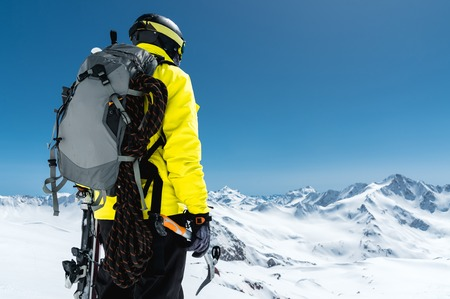 A mountaineer man holds an ice ax high in the mountains covered with snow. View from the back. outdoor extreme outdoor climbing sports using mountaineering equipment Banque d'images