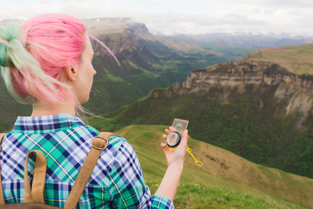 A hipster girl traveled with a blogger in a plaid shirt and with multi-colored hair using a compass in the background in the background of the Caucasian landscape with a plateau