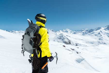 A mountaineer man holds an ice ax high in the mountains covered with snow. View from the back. outdoor extreme outdoor climbing sports using mountaineering equipment Stock Photo
