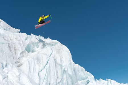 A jumping skier jumping from a glacier against a blue sky high in the mountains. Professional skiing Stock Photo