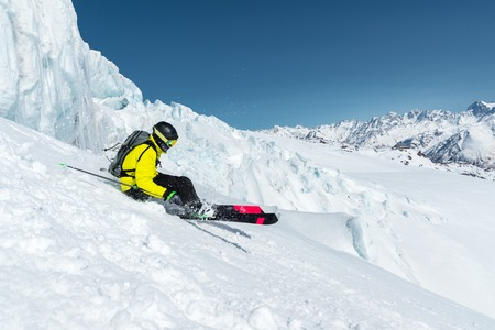The total length of skiing on fresh snow powder. Professional skier outside the track on a sunny day against the background of the glacier Banco de Imagens