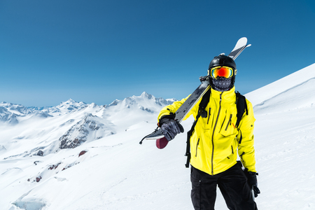 A portrait of a skier in a protective helmet and glasses is a mask and scarf with skis on his shoulder in the snow-capped mountains of the Caucasus. Skiing, 스톡 콘텐츠