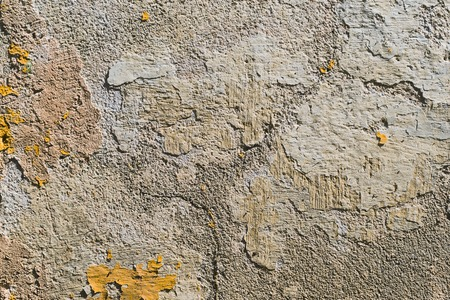 Textured grunge background. Volumetric plastered wall with a multilayer cracked coating. Orange chips on the whitewashed wall. Grunge texture with a deep pattern