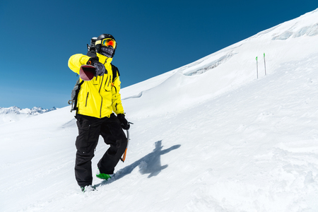 A portrait of a skier in a protective helmet and glasses is a mask and scarf with skis on his shoulder in the snow-capped mountains of the Caucasus. Skiing, Stock Photo