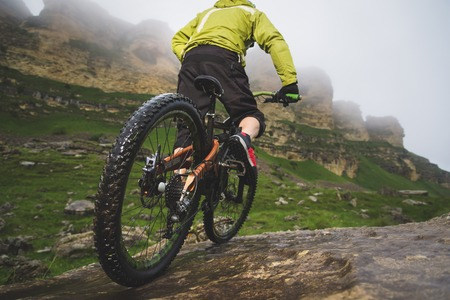 Legs of bicyclist and rear wheel close-up view of back mtb bike in mountains against background of rocks in foggy weather. The concept of extreme sports 版權商用圖片