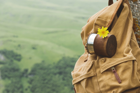 Hipster yellow vintage backpack with a mug fixed on it with a mug close-up front view. Travelers travel bag in the background of a mountain landscape