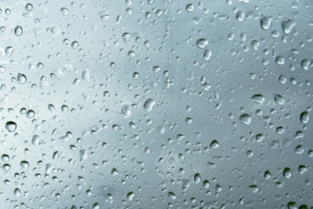Blurred textured background of window panes with a cloudy background. Natural pattern from a drop of rain on a cloudy background Stock Photo