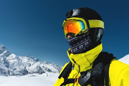 Close-up portrait of a skier in a mask and helmet with a closed face against a background of snow-capped mountains and blue sky 版權商用圖片 - 105653759