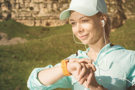 Portrait of a smiling young fitness girl in a cap and headphones checking her smart clock while sitting outdoors against a background of rocks Stock Photo