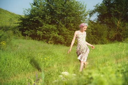 A cute cheerful young girl in a light cotton dress strolls along the country road against the backdrop of summer greenery at sunset Imagens