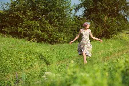 A cute cheerful young girl in a light cotton dress strolls along the country road against the backdrop of summer greenery at sunset Stockfoto