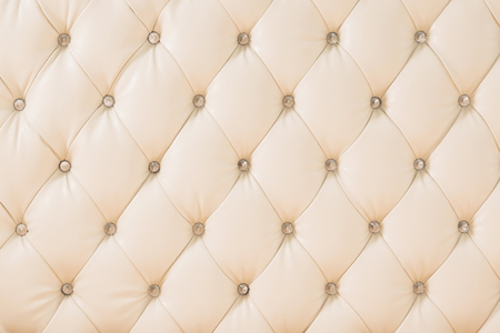 Beige soft tapestry pattern background with symmetrical buttons on the corners of diamonds. Soft and expensive furniture elements. Luxury background