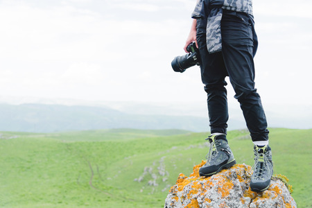 Photographer holding a camera outdoors. Girl on nature Stock Photo