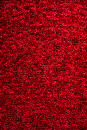 Texture of a dark red carpet. Close-up of gradient light. Stock Photo
