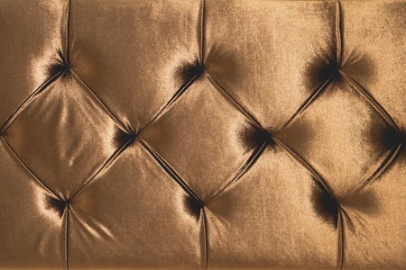 Beige soft textile background with symmetrical buttons on the corners of diamonds. Soft and expensive furniture elements. Luxury background
