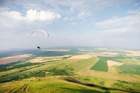A white-orange paraglider flies over the mountainous terrain