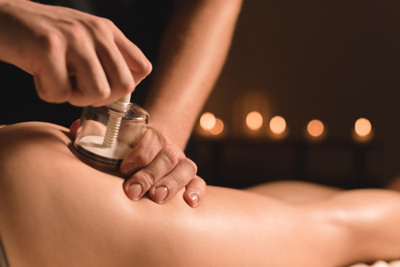 Close-up Hardware cosmetology. Vacuum massage procedure. Male hands install vacuum banks. Close-up of anti-cellulite treatment of a young woman Stock Photo