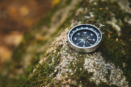 Magnetic compass with a black dial on a wild stone covered with green moss. The concept of finding the way and navigation Stock Photo