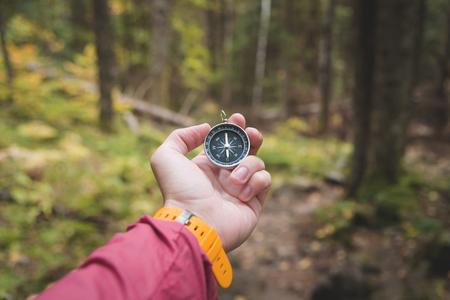 Eine schöne männliche Hand mit gelbem Uhrenarmband hält einen Magnetkompass im Nadelwald im Herbst. Das Konzept, den Weg und die Wahrheit zu finden Standard-Bild
