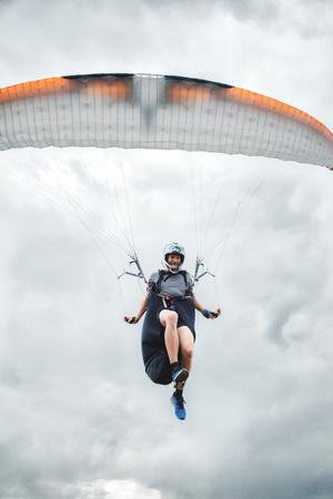 Nahaufnahme eines professionellen Gleitschirms mit einem Kokon auf den Schultern fliegt im Sprung über die Kamera. Gleitschirmsportkonzept Standard-Bild