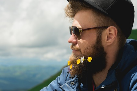 Close-up portrait of a cheerful bearded man in sunglasses and a gray cap with wildflowers in a beard. Soft brutality and good masculinity