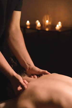 Mens hands make a therapeutic neck massage for a girl lying on a massage couch in a massage spa with dark lighting. Close-up. Dark Key Stock Photo