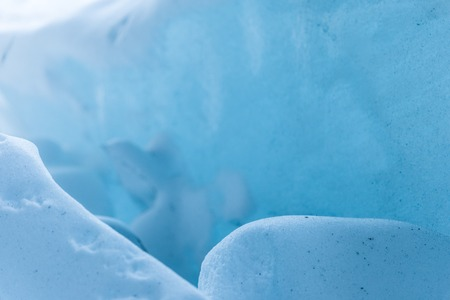 Close-up pieces of ice showered in the ice grotto of a glacier. The destruction of the glacier. Global warming. Small DOF